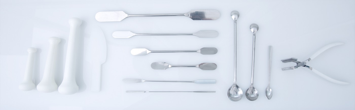 Ein Foto in dem schön sortiert diverse Laborgerätschaften sichtbar sind. Von links nach rechts befinden sich pistille diverser Größen, dann diverse Spatel, daneben Löffel unterschiedlicher Größe und ganz rechts eine Salbenquetsche