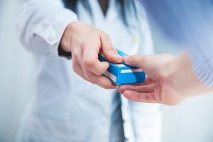 ein Apotheker übergibt einem Patienten ein Medikament