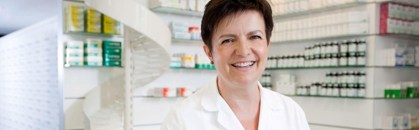 Mitarbeiterin aus dem Verkauf, die lächeld ins Bild sieht. im Hintergrund diverse nahrungsergänzungsmittel